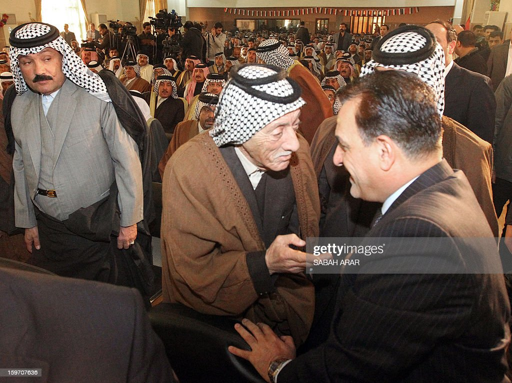 Iraqi Deputy Interior Minister Adnan al-Assadi (R) attends a meeting headed by the Sunni and Shiite clan leaders in Baghdad to listen to the demands of the protestors in an attempt to halt the escalation of demonstrations in Sunni areas, on January 19, 2013. AFP PHOTO / SABAH ARAR