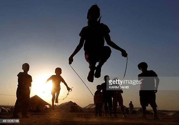 Iraqi displaced children play at sunset at a temporary camp set up to shelter people fleeing violence in northern Iraq on June 27 2014 in Aski kalak...