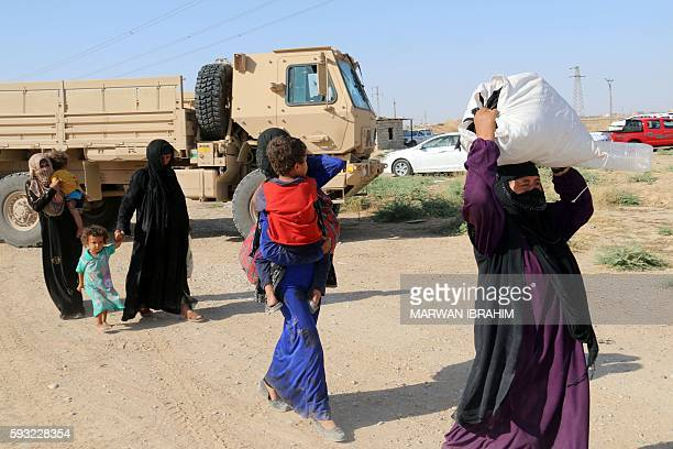 Iraqi displaced families arrive in an area controlled by the Peshmerga forces some 55 kilometres west of Iraqi city of Kirkuk on August 21 2016 after...