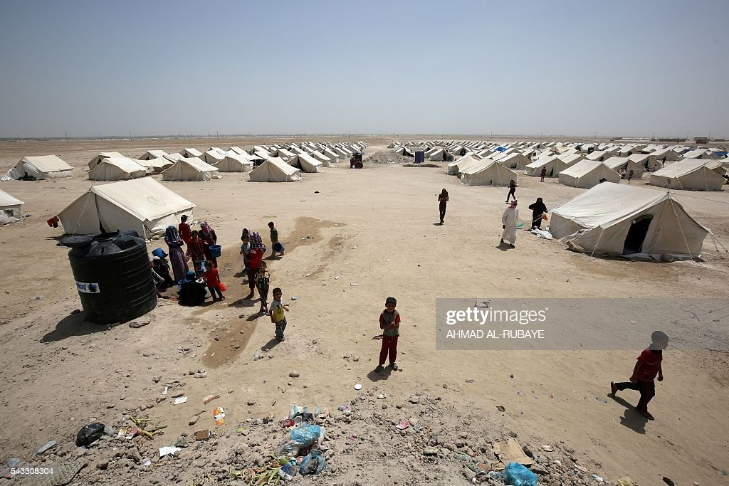 Iraqi displaced from the city of Fallujah are seen at a newly opened camp where hundreds of displaced Iraqis are taking shelter in Amriyat al-Fallujah on June 27, 2016, south of Fallujah. Iraqi forces on June 26 wrapped up operations in Fallujah and declared the area free of jihadists from the Islamic State (IS) group after a month-long operation. The government said the destruction caused by the fighting was limited and vowed to do its utmost to allow the tens of thousands of displaced civilians to return to their homes. RUBAYE