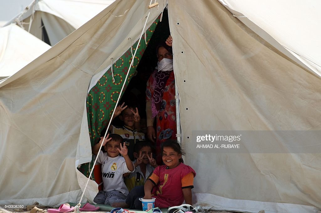 Iraqi displaced from the city of Fallujah gesture to the camera at a tent at a newly opened camp where hundreds of displaced Iraqis are taking shelter in Amriyat al-Fallujah on June 27, 2016, south of Fallujah. Iraqi forces on June 26 wrapped up operations in Fallujah and declared the area free of jihadists from the Islamic State (IS) group after a month-long operation. The government said the destruction caused by the fighting was limited and vowed to do its utmost to allow the tens of thousands of displaced civilians to return to their homes. RUBAYE