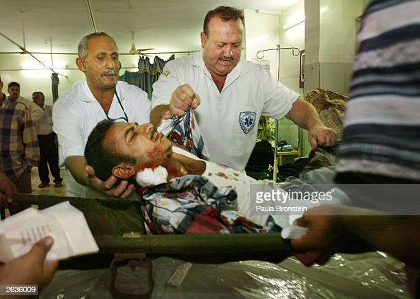 Iraqi doctors carry a bombing victim into the emergency room at Al Yarmouk hospital October 23 2003 in Baghdad Iraq The injured person was caught in...