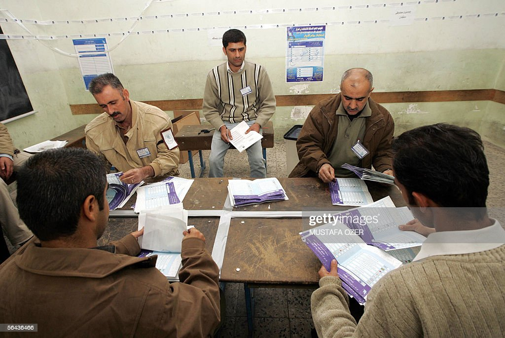Iraqi election officials count the votes at a polling station in the northern Kurdish city of Suleimaniya 15 December 2005 Iraqis turned out in force...