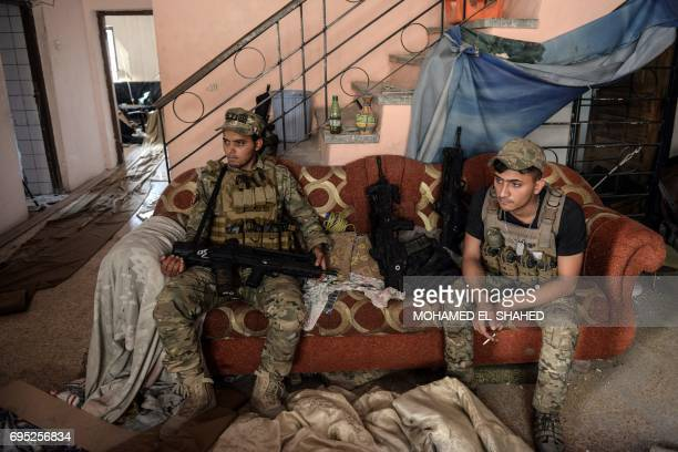 Iraqi elite Rapid Response Division members take a break inside a building in Mosul's western AlShifa district on June 12 2017 / AFP PHOTO / MOHAMED...