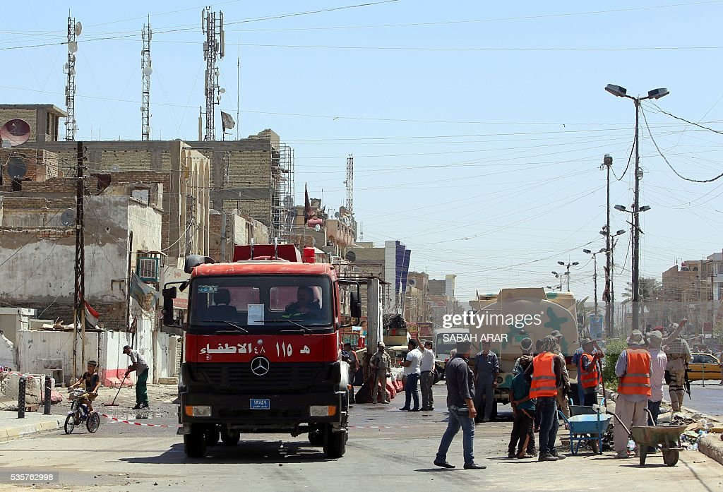 Iraqi emergency personnel and municipality employees clean up the site of a car bombing that targeted a market area in the capital Baghdad on May 30, 2016. Three bomb blasts in and around Baghdad killed at least 11 people and wounded dozens in the latest wave of attacks to hit the Iraqi capital, police said. / AFP / SABAH