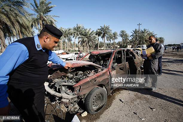 Iraqi emergency responders inspect debris at the site of a truck bomb that exploded at a crowded checkpoint in the Iraqi city of Hilla south of...