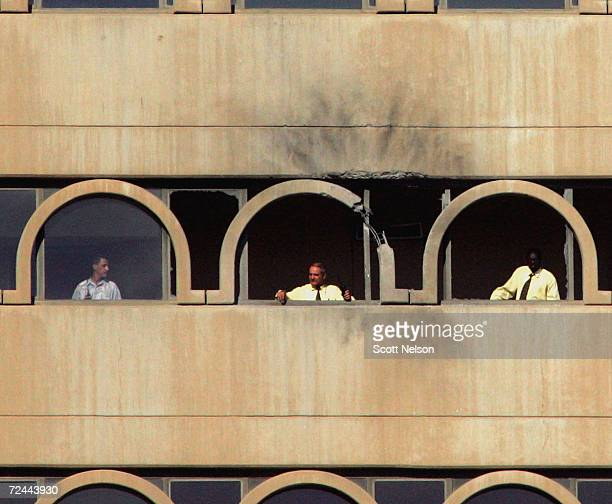 Iraqi employees of the Sheraton hotel in Baghad peer out from the damaged 10th floor hallway following a rocket attack on the building July 02 2004...