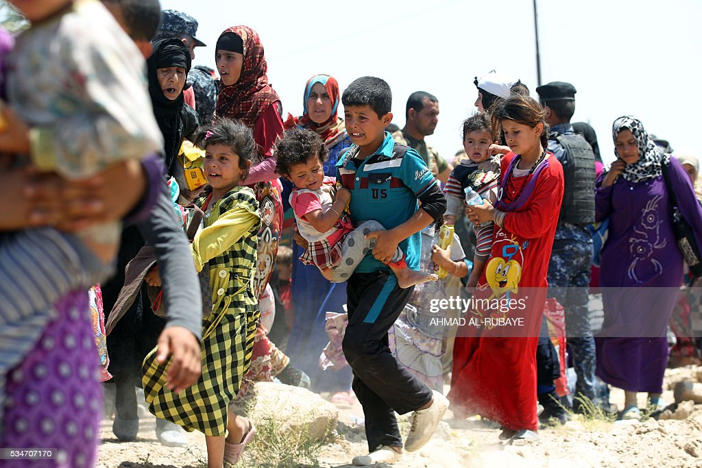 Iraqi families are pictured near al-Sejar village, in Iraq's Anbar province, after fleeing the city of Fallujah, on May 27, 2016, during a major operation by Pro-government forces to retake the city of Fallujah, from the Islamic State (IS) group. Hundreds of people fled the Fallujah area with the help of Iraqi forces, officials said. / AFP / AHMAD
