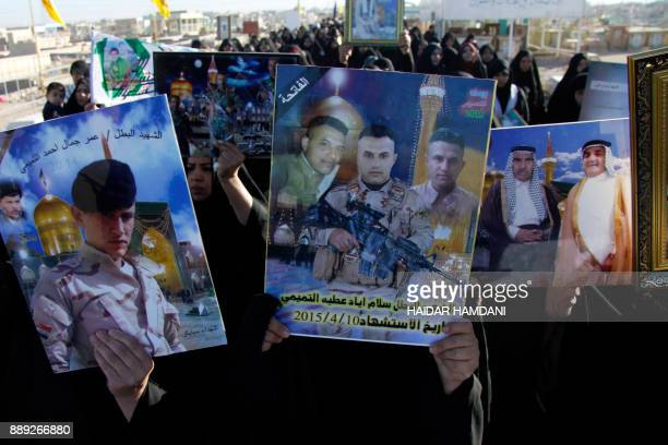 Iraqi families carry portraits of their relatives who died in the combat against the Islamic State group at the Wadi alSalam cemetary in the Shiite...