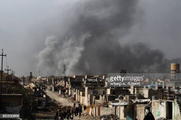TOPSHOT Iraqi families leave Mosul's Nablus neighbourhood on March 12 during an offensive by security forces to retake the western parts of the city...