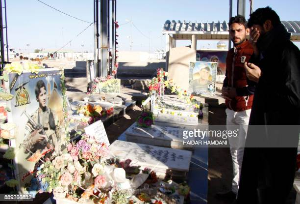 Iraqi families pray over the grave of a fighter killed in the combat against the Islamic State group at the Wadi alSalam cemetary in the Shiite holy...