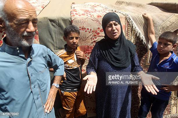 Iraqi families who fled the city of Ramadi after it was seized by Islamic State group militants talk to journalists at a camp housing displaced...