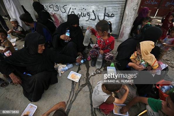 Iraqi families who fled the town of Hawija eat food as they take refuge in the nearby town of Sharqat around 80 kilometres south of the city of Mosul...