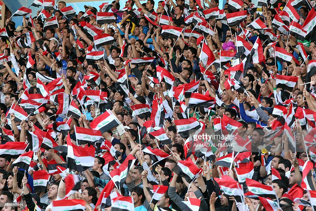 Iraqi fans wave their national flag as their team plays a friendly football match against Syria at the al-Shaab Stadium in Baghdad on March 26, 2013. Iraq defeated Syria 2-1, days after FIFA lifted a ban on Baghdad hosting international matches, in just the second friendly to be played in the Iraqi capital since the 2003 invasion.
