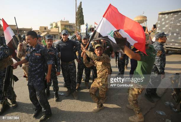 TOPSHOT Iraqi federal police members celebrate in the Old City of Mosul on July 9 2017 after the government's announcement of the 'liberation' of the...