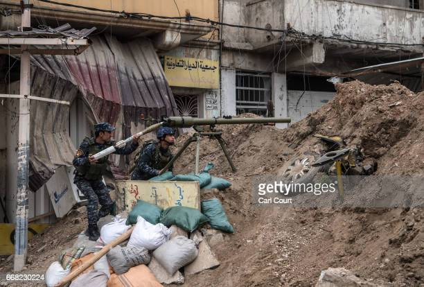 Iraqi federal policemen prepare to fire an antitank rocket launcher at an Islamic State position during the battle to recapture west Mosul on April...