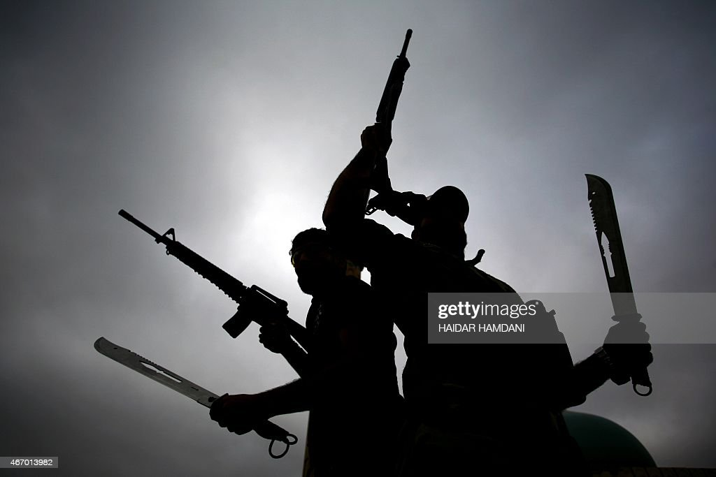 Iraqi fighters from the Saraya alSalam a group formed by Iraqi Shiite Muslim cleric Moqtada alSadr wave their weapons as they leave the holy city of...