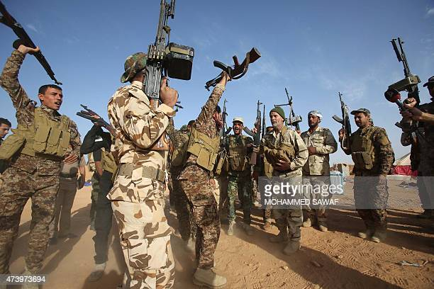 Iraqi fighters from the Shiite Muslim AlAbbas popular mobilisation unit hold up their weapons in the area surrounding the village of Nukhayb in the...