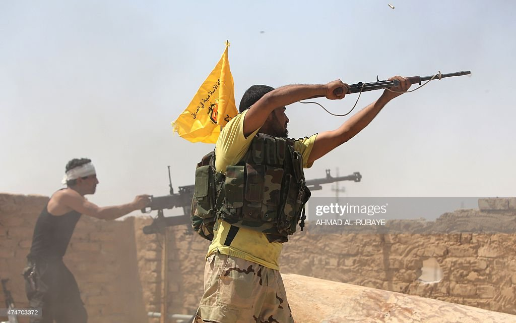 Iraqi fighters from the Shiite popular mobilisation unit fire their weapons in the outskirts of Baiji refinery north of Tikrit in the Salahaddin...