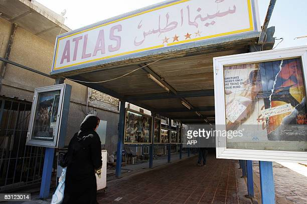 Iraqi film goers look at the posters of current or upcoming presentations at the entrance of the Atlas cinema one of the most famous movie theatres...