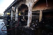 Iraqi firefighters extinguish fire at a market near the Sayyid Mohammed shrine in the Balad area located 70 kilometres north of Baghdad on July 8 in...