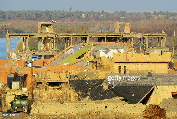 Iraqi flags fly above destroyed buildings in the rural Husayba alSharkiya area east of Anbar province's capital Ramadi as Iraqi security forces...