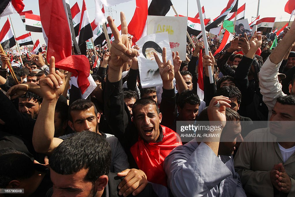Iraqi followers of Shiite Muslim cleric Moqtada al-Sadr flash the sign for victory and wave their national flag during a protest on March 16, 2013, in the city of Kut, south of the capital Baghdad, on the occasion of the tenth anniversary since the US-led invasion of Iraq. Demonstrators also called for the Iraqi government to provide basic services, to release prisoners they say are wrongfully held, and an end to oppression.