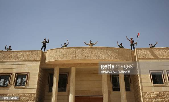 Iraqi forces celebrate on the rooftop of a building in the town of Sharqat around 80 kilometres south of the city of Mosul on September 23 the day...
