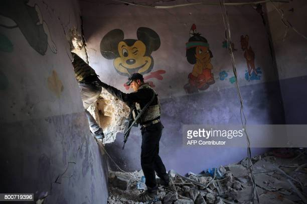 TOPSHOT Iraqi forces climb through a hole in the wall as they advance through the Old City of Mosul on June 25 during the ongoing offensive to retake...