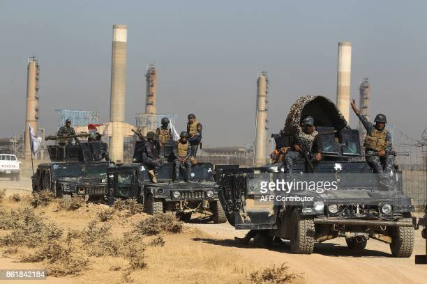 TOPSHOT Iraqi forces drive past an oil production plant as they head towards the city of Kirkuk on October 16 2017 / AFP PHOTO / AHMAD ALRUBAYE