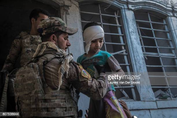Iraqi forces evacuate a boy and his family that they discovered in alNuri mosque complex on June 29 in Mosul Iraq The Iraqi Army Special Operations...