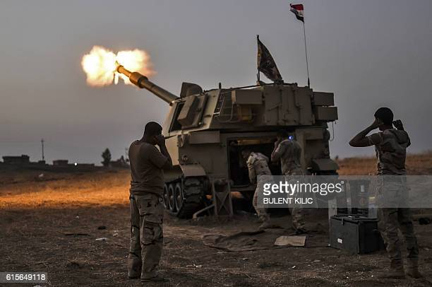 TOPSHOT Iraqi forces fire a M109 selfpropelled howitzer towards the village of AlMuftuya from a position in Kani alHarami some 35 kilometres of Mosul...