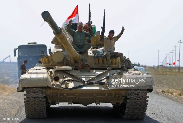 Iraqi forces flash the sign for victory as they drive towards Kurdish peshmerga positions on on the southern outskirts of Kirkuk on October 15 2017...