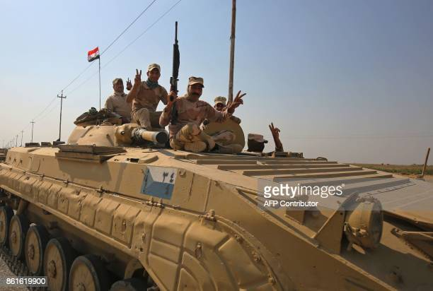 Iraqi forces flash the sign for victory as they drive towards Kurdish peshmerga positions on October 15 on the southern outskirts of Kirkuk The...