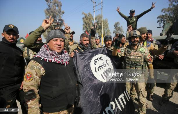 Iraqi forces flash the sign for victory while holding an Islamic State group flag on February 23 as they enter Mosul airport on the southern edge of...
