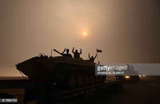 TOPSHOT Iraqi forces flash the Vsign as they stand on an infantry fighting vehicle loaded on a truck driving through the AlShura area south of Mosul...