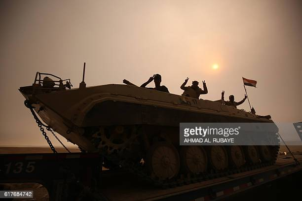 Iraqi forces flash the Vsign as they stand on an infantry fighting vehicle loaded on a truck driving through the AlShura area south of Mosul on...