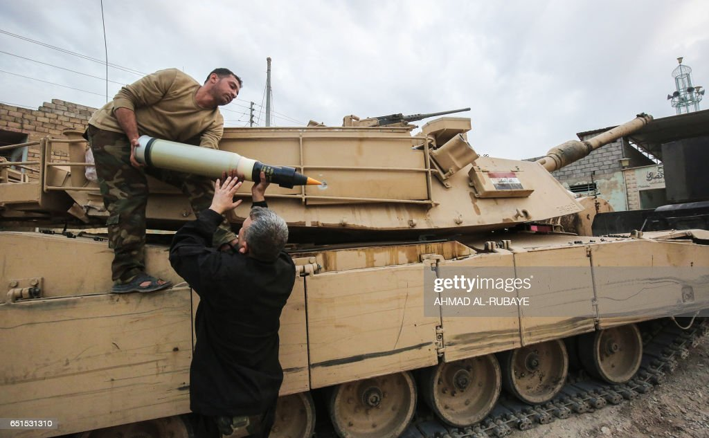 الابرامز في معركة الموصل  Iraqi-forces-load-ammunition-shells-onto-an-m1-abrams-tank-during-the-picture-id651531310
