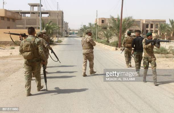 Iraqi forces members patrol during a military operation to push out Islamic State group jihadists from the village of Anna in the northwestern Anbar...