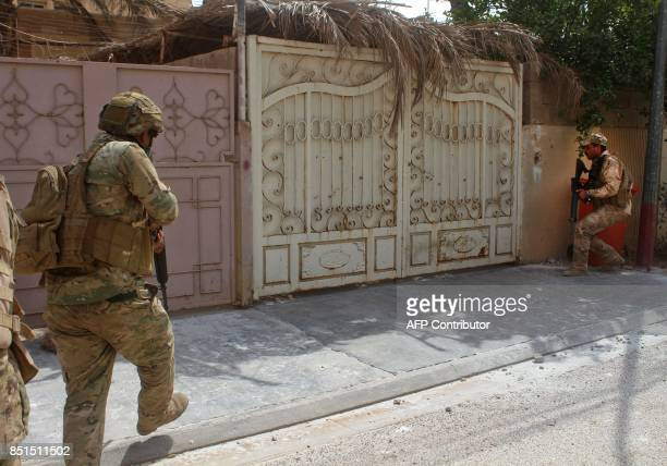 Iraqi forces members prepare to enter a building during a military operation to push out Islamic State group jihadists from the village of Anna in...