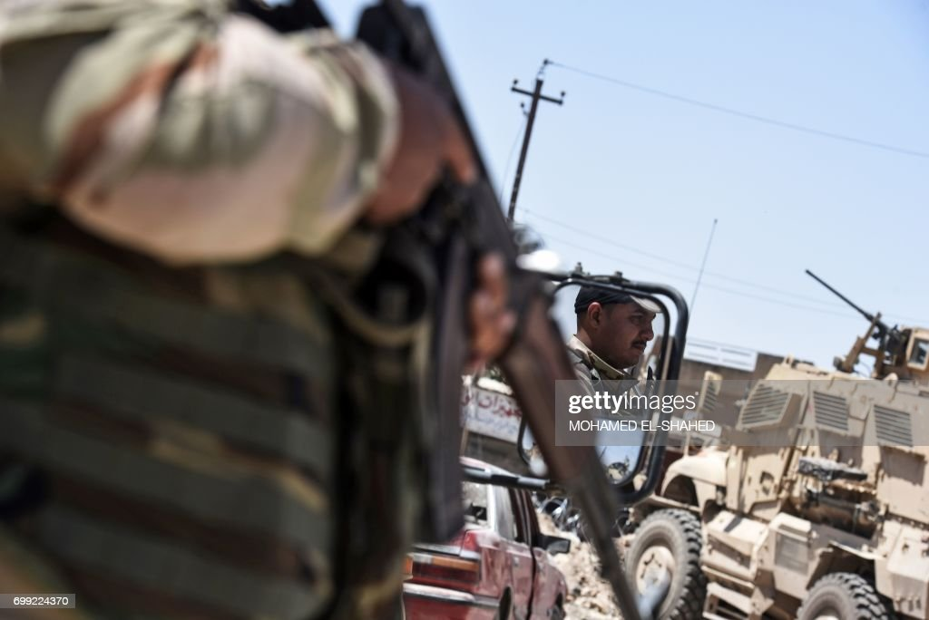 TOPSHOT - Iraqi forces patrol a street near Mosul's Old City on June 21, 2017, during the ongoing offensive to retake the last district still held by the Islamic State (IS) group. /
