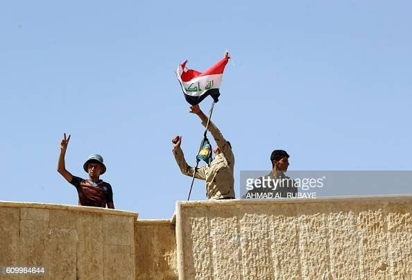 Iraqi forces raise their national flag as they celebrate on the rooftop of a building in the town of Sharqat around 80 kilometres south of the city...