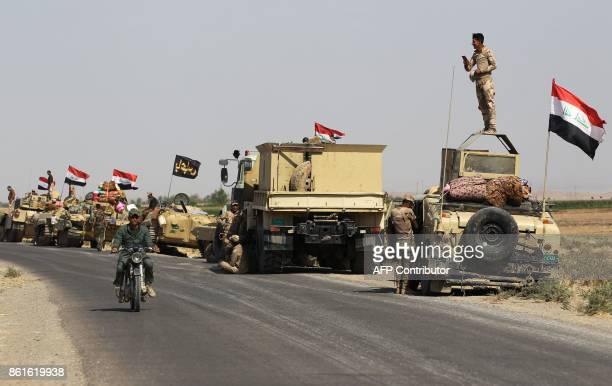 TOPSHOT Iraqi forces rest on the road as they drive towards Kurdish peshmerga positions on October 15 on the southern outskirts of Kirkuk The...