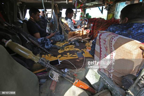 Iraqi forces sit in a vehicle as they gather on a river bank across from Kurdish peshmerga positions on October 15 on the southern outskirts of...