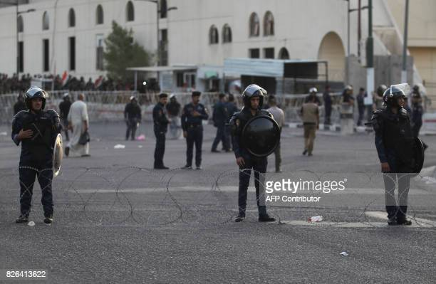 Iraqi forces stand guard outside the Green zone as supporters of cleric Moqtada alSadr attend a demonstration in Tahrir Square central Baghdad on...