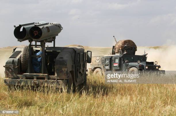 Iraqi forces vehicles one of them mounted with a homemade rocket launcher advance towards the AlHaramat neighbourhood north of Mosul on May 7 during...