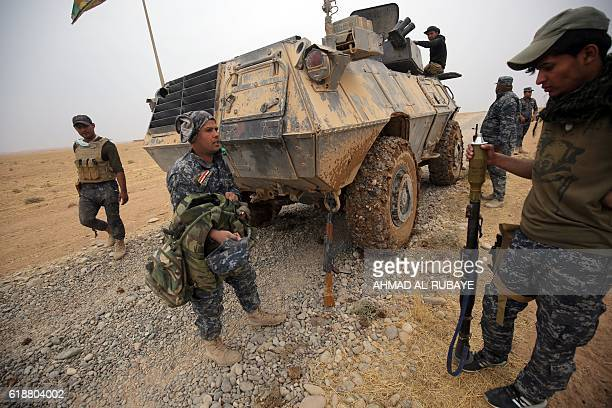 Iraqi forces wait next to their armoured vehicle in the alShura area south of Mosul on October 28 2016 during an operation to retake the main hub...