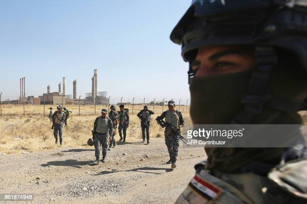 TOPSHOT Iraqi forces walk in front of an oil production plant as they head towards the city of Kirkuk during an operation against Kurdish fighters on...