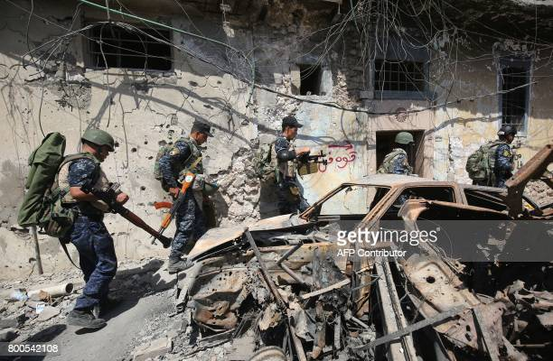 TOPSHOT Iraqi forces walk past charred vehicles as they advance through the Old City of Mosul on June 24 2017 during the ongoing offensive to retake...