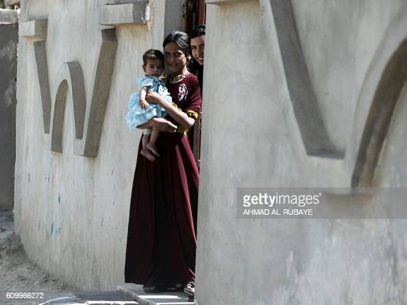 Iraqi girls look out of their house in the town of Sharqat around 80 kilometres south of the city of Mosul on September 23 the day after Iraqi...